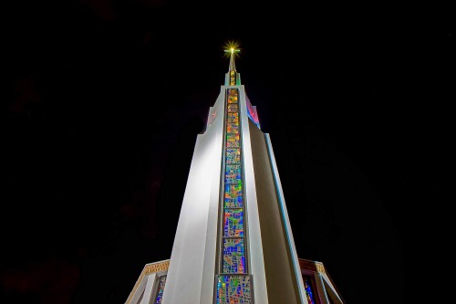 Modern church in America with large stained glass window and tall white tower spire religious architecture