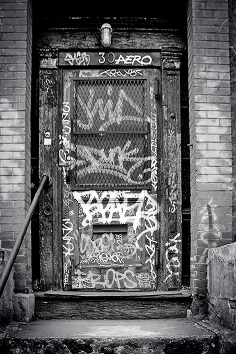 Old Door in New York City covered in Graffiti tags in black and white