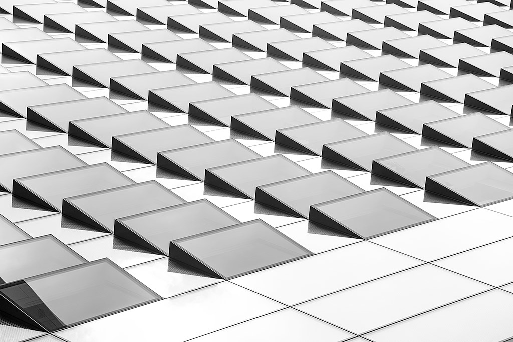 Side of modern office skyscraper buildings architecture with Large glass windows and triangle panels in black and white minimal design