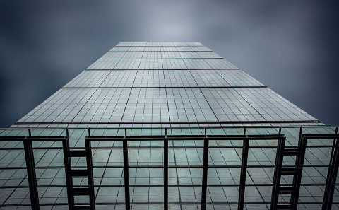 Modern Skyscraper Office Building with Glass facade and dark grey sky viewed from below