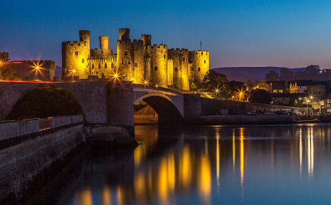 Conwy Castle in North Wales United Kingdom at night with the Lights Reflecting in the river below