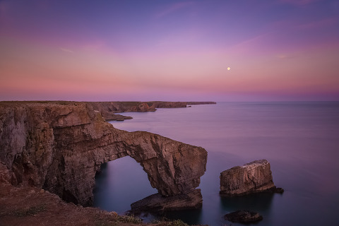 Green Bridge of Wales arch at sunset purple sky and moon landscape