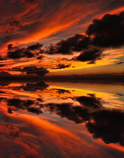 Red Sky Sunset with Clouds reflected on the Still waters at dusk