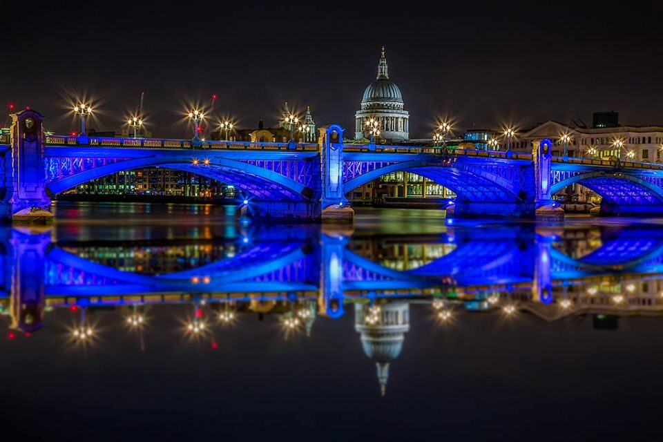 London Bridge And St Pauls Cathedral reflected at night in blue lights in the River Thames