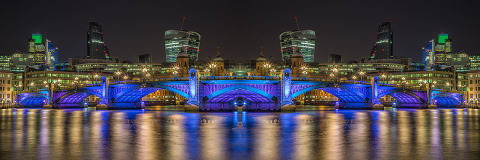 London Bridge and St Pauls Cathedral Building Reflected in River Thames at night in Blue Lights Panorama