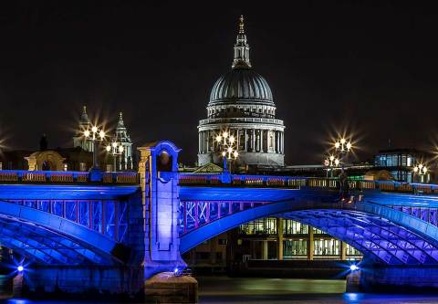 London Bridge and St Pauls Cathedral Building Reflected in River Thames at night in Blue Lights