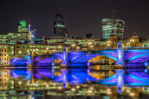 London Bridge and Walkie Talkie Building Reflected in River Thames at night in Blue Lights