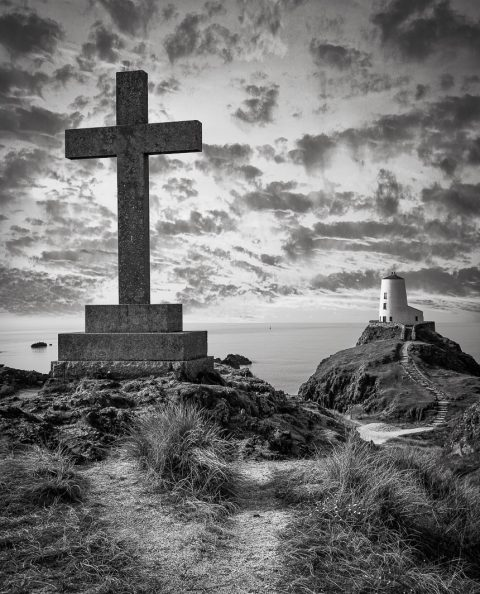 Trwn Du Lighthouse in Anglesey Wales with stone cross black and white landscape