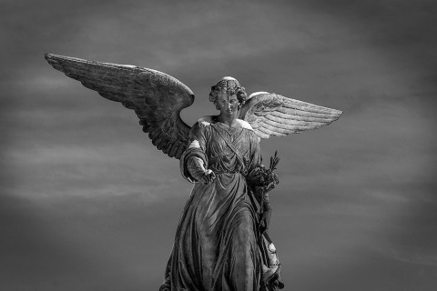 the Bethesda angel statute covered in snow in central park in new york city at winder in black and white