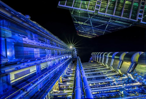 London Architecture night scene looking up at Lloyds Building skyscraper and modern office building in lights.