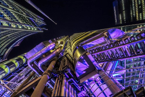 Looking up at the Lloyds Building at night lit up in colored lights in London England