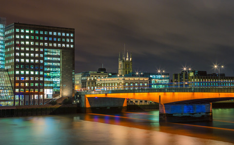 London Bridge at night in orange with the River Thames at night in England