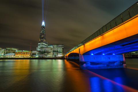 London Bridge at night in orange with the River Thames and the Shard Building with Lazer at night in England