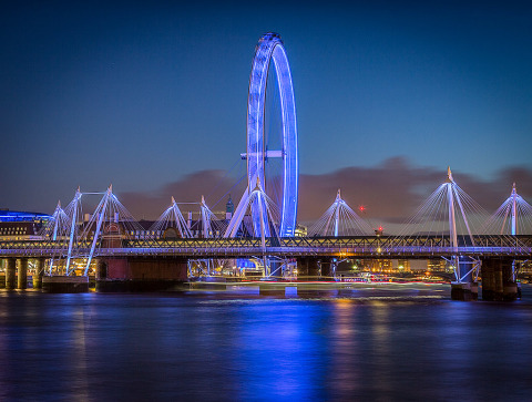 The London Eye Ferris wheel in England at night in blue lights on the River Thames with Hungerford Bridge in the foreground