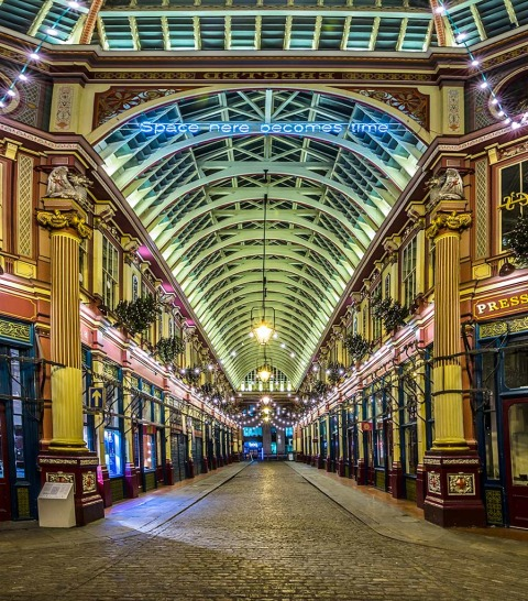 Looking through the cobbled alleyway in Leadenhall Market in City of London with shops and lights at night