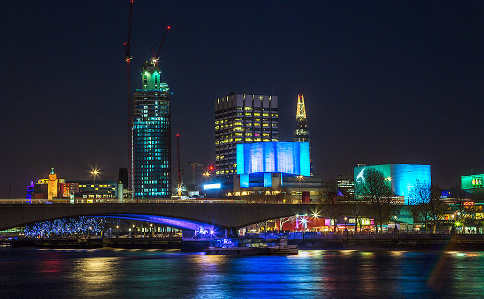 London Bridge over the River Thames at night with the Hayward Gallery and Shard Building in England
