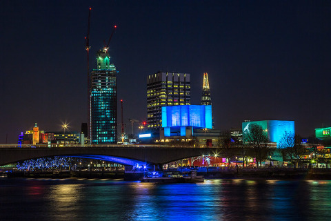 London cityscape skyline at night viewed from embankment beside the River Thames including theShard skyscraper and South Bank Centre Hayward Gallery in blue lights