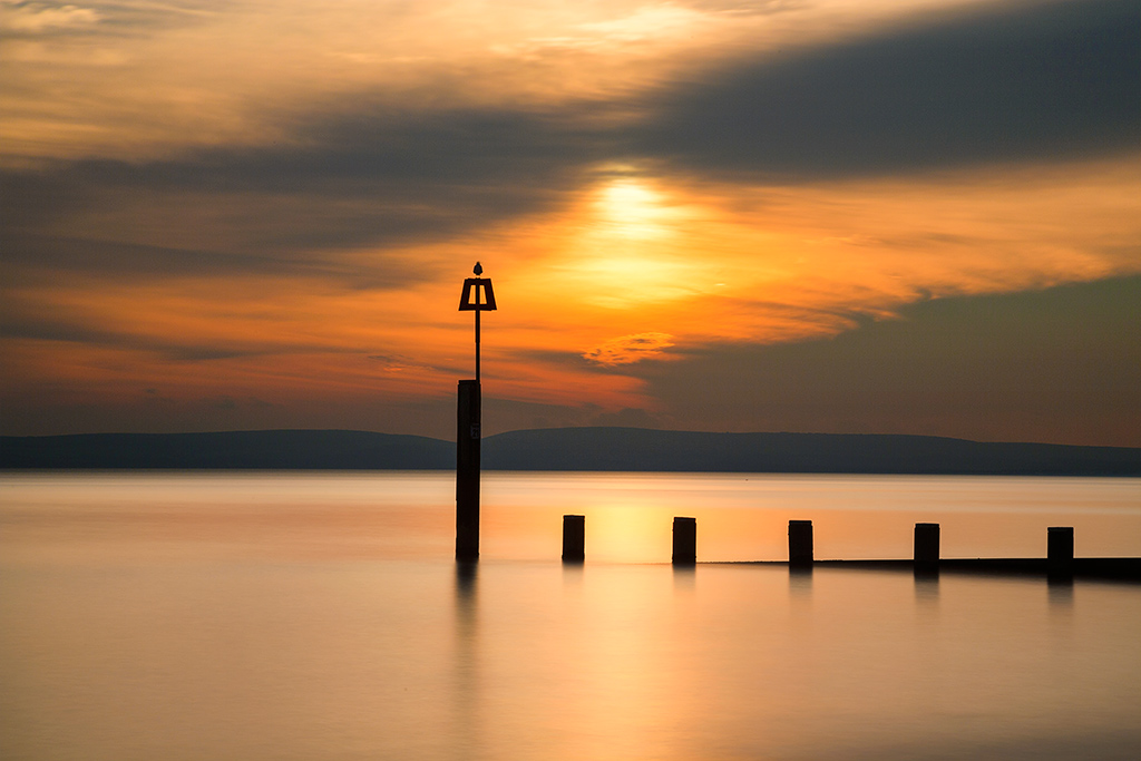 Seascape long exposure at sunset of wooden groyne and ocean sea with fence and seagull bird