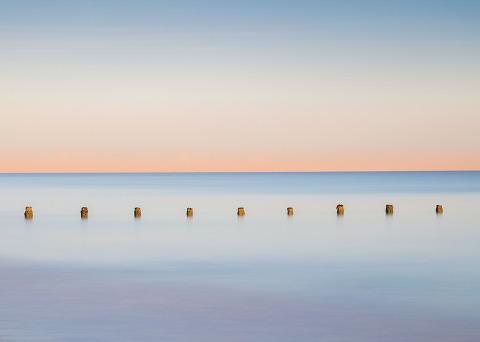 Seascape minimal sea groynes along English coast long exposure at sunset