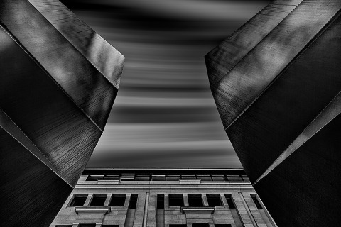architecture black and white long exposure of building with fast moving dramatic clouds