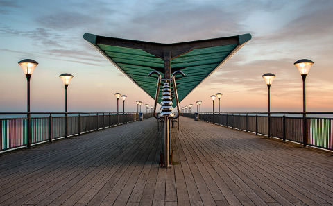 Architecture of Boscombe Pier jetty wooden walkway over the ocean in England at sunset