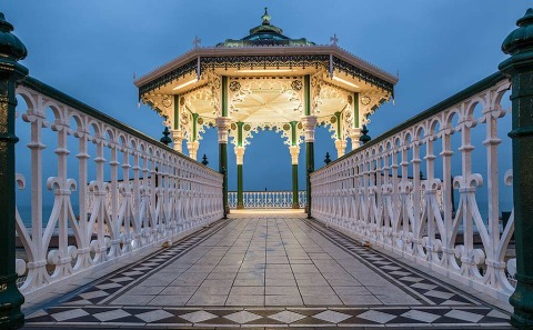 architecture of old fashioned ornate iron pavilion pagoda and tiled floor walkway in Brighton England at dawn by the ocean