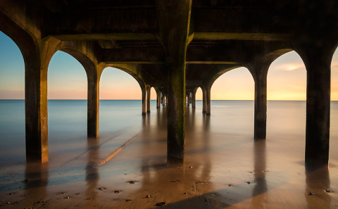 Architecture under Boscombe Pier jetty wooden walkway over the ocean in England at sunset long exposure