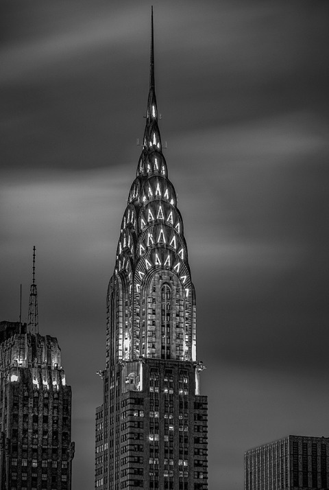 art deco chrysler building in Manhattan New York City in lights at night with long exposure sky in black and white