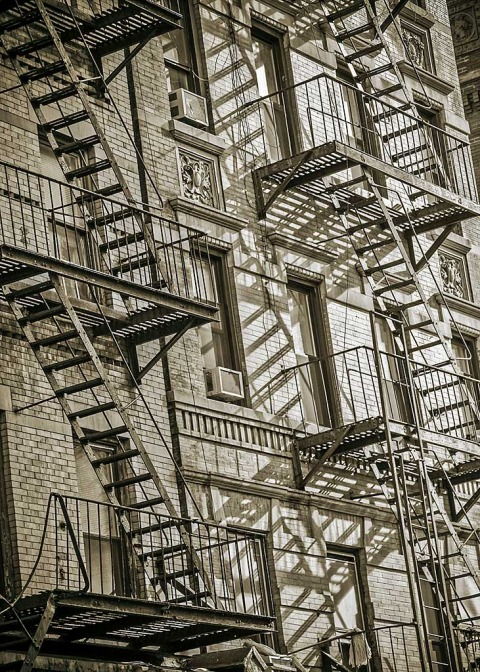 metal fire escapes outside new york city apartment building in sepia with shadows NYC
