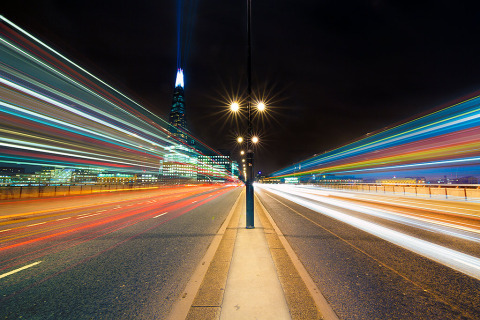 On London Bridge roadway with Car light trails street star lamps and the Shard Building with lazer in England