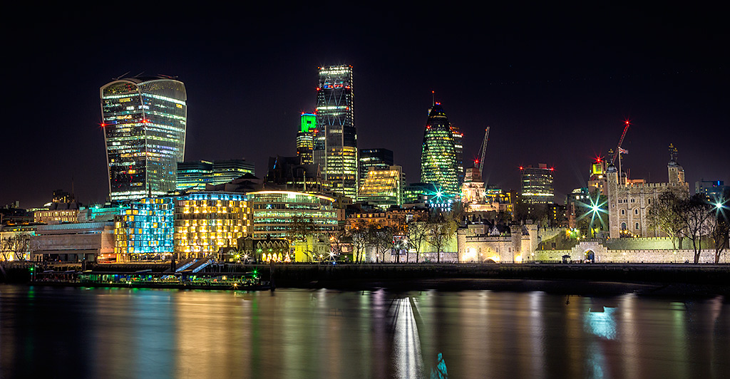 River Thames ad Tower of London at night with the Gherkin St Marys Axe Walkie Talkie and and Shard Building in England