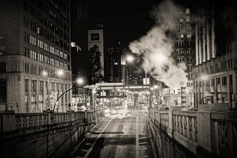 street scene of park avenue in midtown manhattan in new york city with smoke stacks in black and white