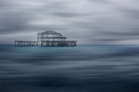 Seascape long exposure old derelict Brighton Pier in England in the Ocean in winter blue hues
