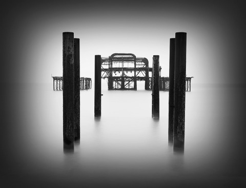 Seascape long exposure old derelict Brighton Pier in England in the Ocean in black and white looking towards the metal structure low key