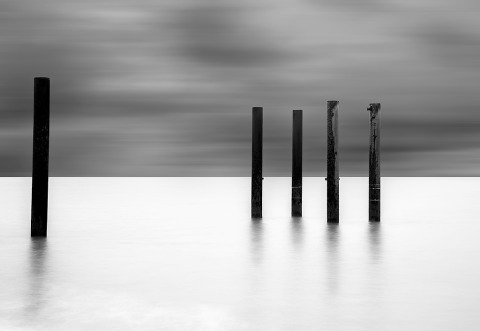 Seascape long exposure black and white minimal ocean with metal poles