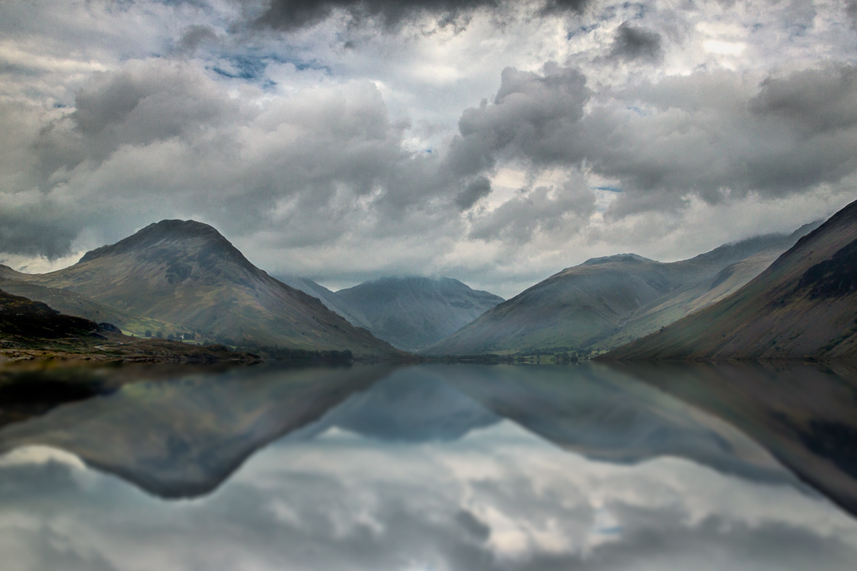landscape of the lake district mountains reflected in a lake in England UK