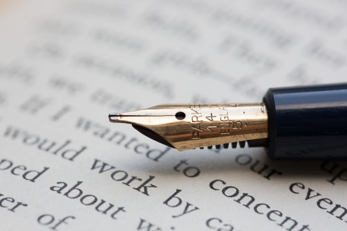 macro of fountain pen on a book page with shallow depth of field