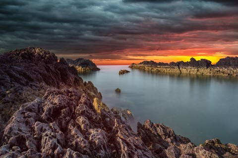 jagged rocks ocean colorful sunset