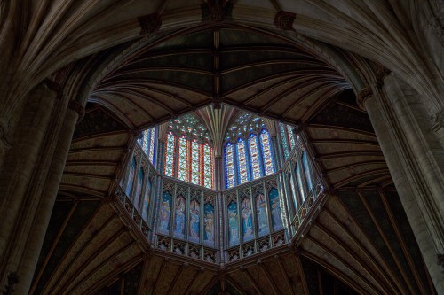 Ornate carved ceiling and stained glass windows in Ely Cathedral in England