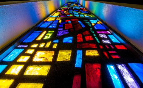 architecture stained glass window of church lit up at night viewed vertically
