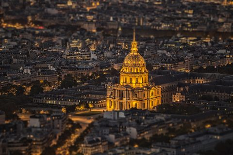 Les Invalides in Paris and City rooftops at night with lights