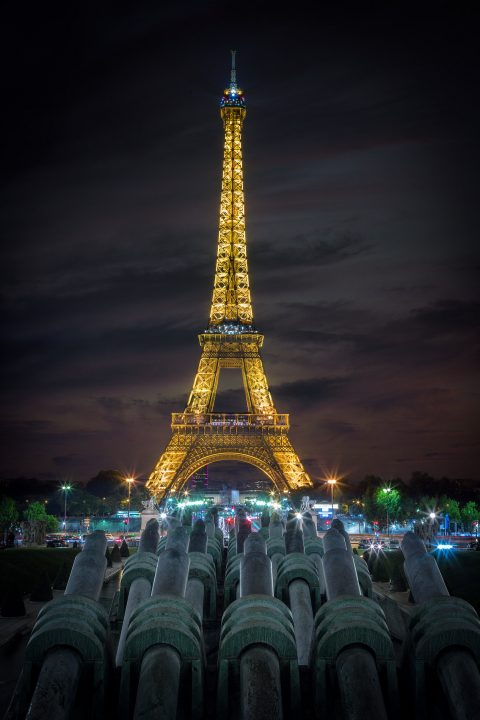 Eiffel Tower at Night in Paris with Lights and cannons viewed from Place de Concorde