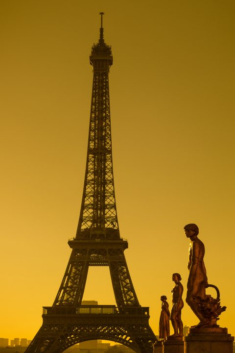 Eiffel Tower and statues in golden sunlight viewed from Place de Concorde