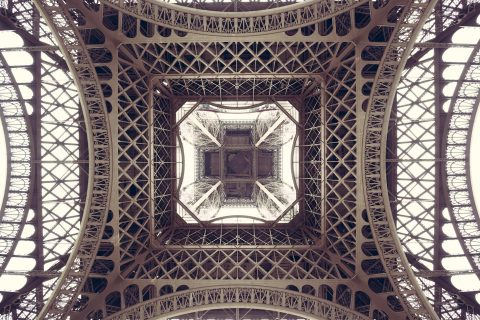 Abstract view of Eiffel Tower centre metalwork from below in muted color tones