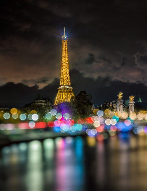 Paris view along river Seine with Eiffel Tower at Night in Lights Bokeh soft focus