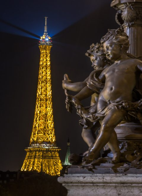Eiffel Tower at nights in lights and statues from Pont Alexandre III