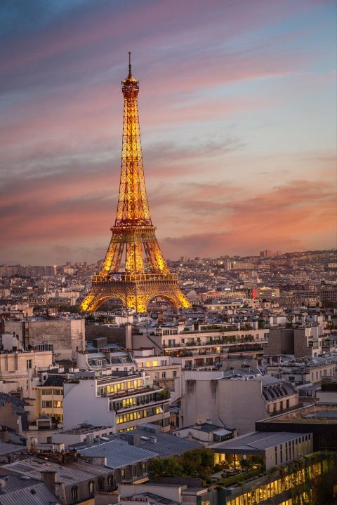 Eiffel Tower in Paris and City rooftops at sunset with lights