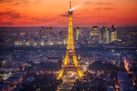 Eiffel Tower in Paris and La Defence Buildings at sunset with lights