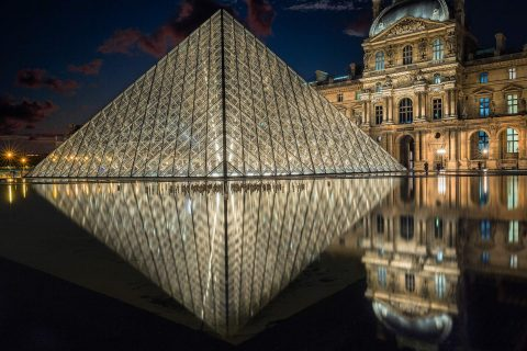 Louvre Museum at night in Paris France reflected