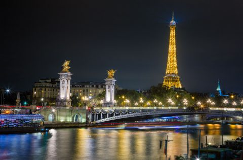 Paris view along river Seine with Eiffel Tower and Pont Alexandre III Bridge at Night in Lights